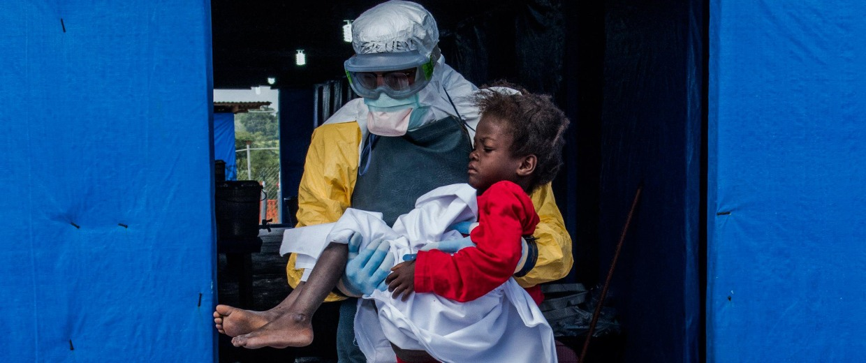 Image: Dr. Steven Hatch carries Blessing Gea, 9, from the suspected ward to the confirmed high-risk ward after a blood test showed her positive for Ebola, at a clinic run by the International Medical Corps.