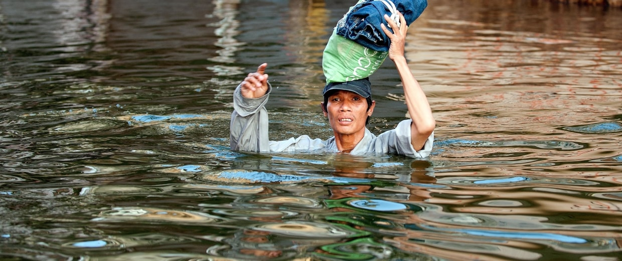 Image: A resident wades through neck-high floodwaters in Rangsit district