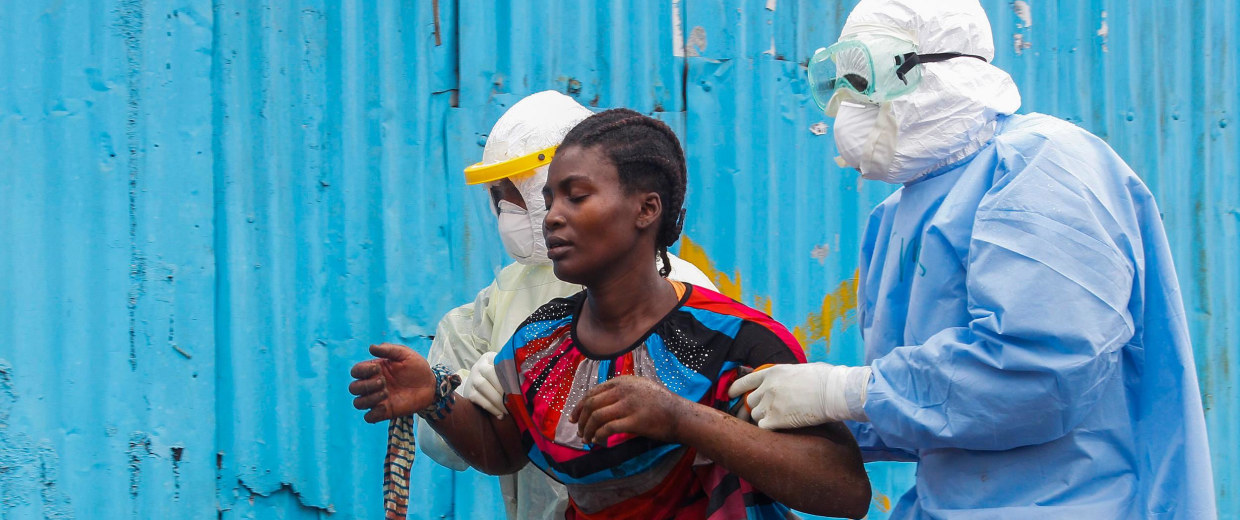 Image: Liberian nurses escort a suspected Ebola patient into the John F. Kennedy (JFK) Ebola treatment center in Monrovia