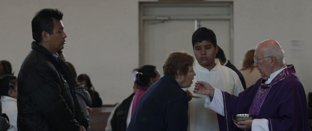 Image: A Catholic priest distributes Holy Communion to the congregation as a green light is lit inside St. Teresa of Avila church in Monterrey
