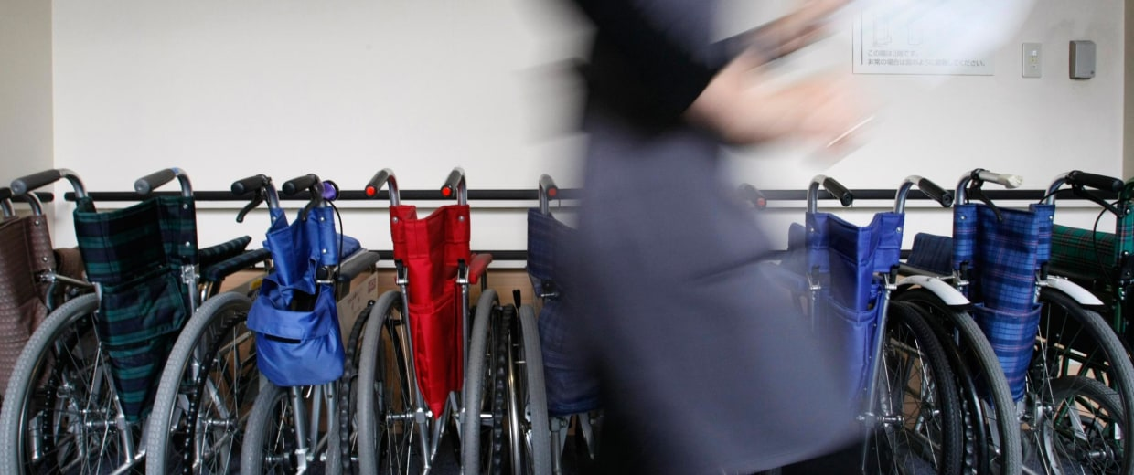 Imag: A staff member walks past wheelchairs at a nursing home.