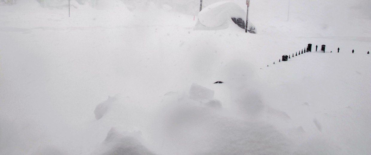 Image: A 4-foot fence and SUV are nearly buried along a street in Buffalo