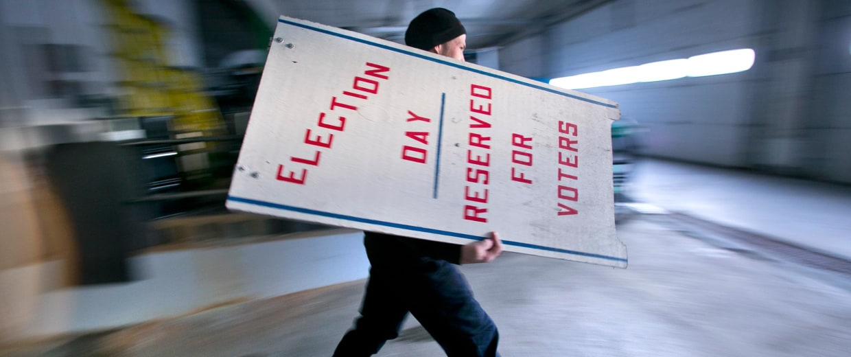 Image: Firefighter Cheyne Hansen takes a sign out of storage at a municipal garage while helping election officials scramble to set up a last-minute polling place