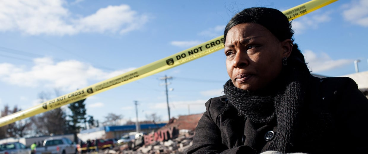 Image: Jessica, an employee at Prime Beauty, on Chambers Road in Dellwood, sits outside the ruins of the store