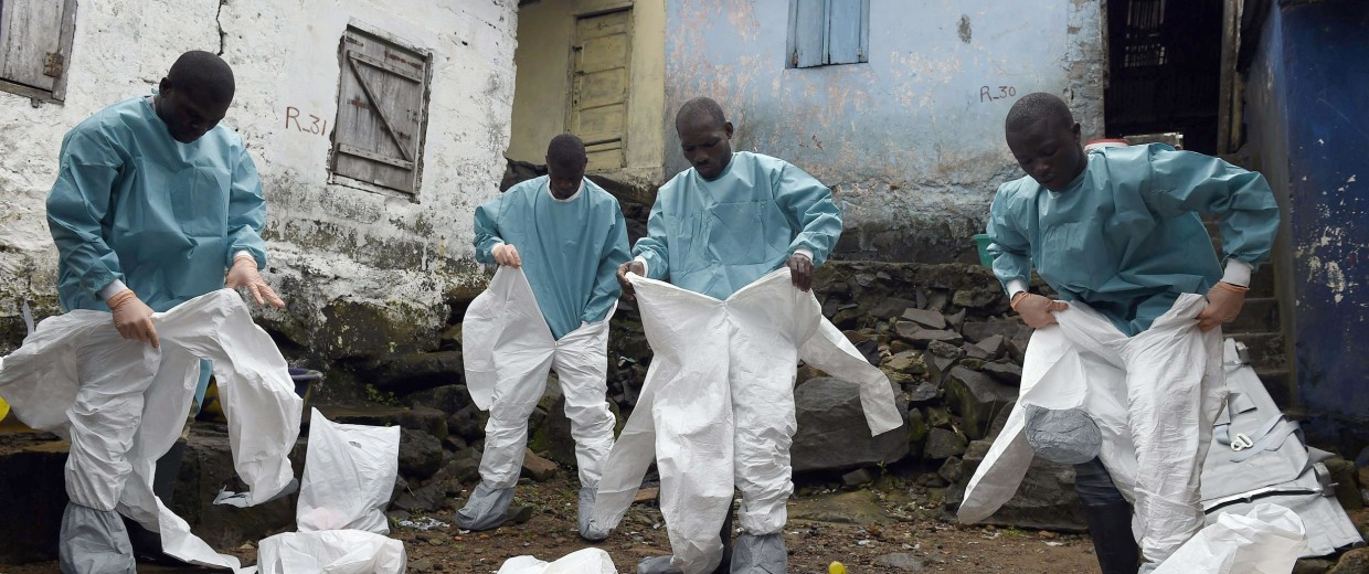 Image: Medical staff members of the Croix Rouge NGO put on protective suits before collecting the corpse of a victim of Ebola