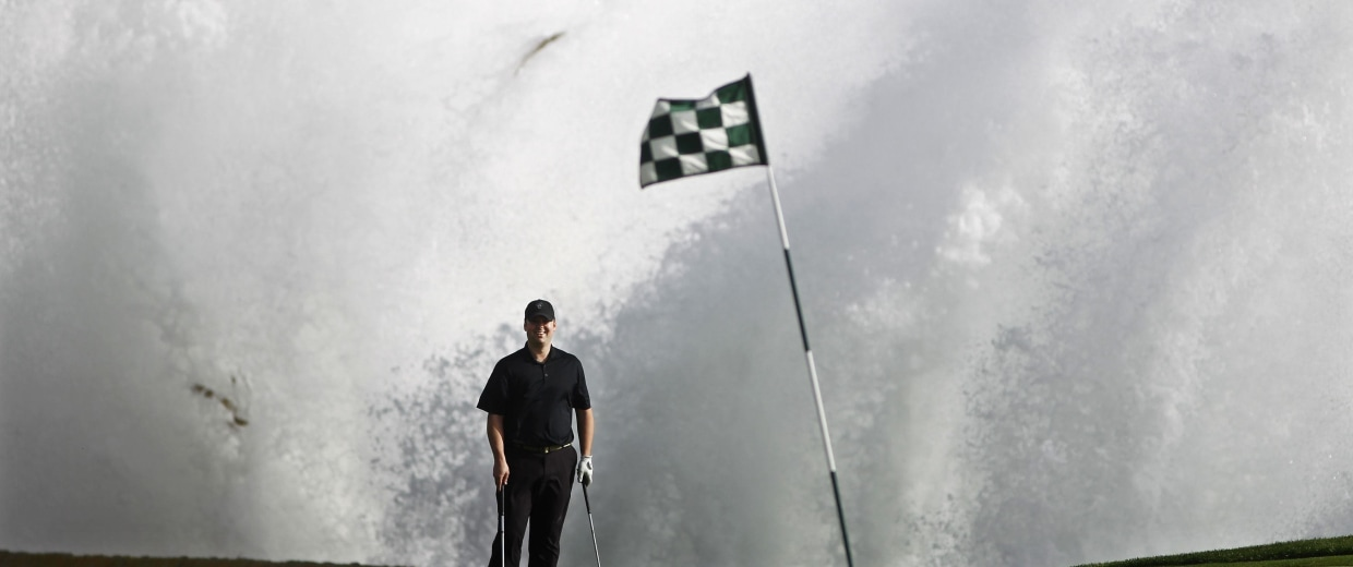 Image: A wave crashes behind Todd Linehan on the 18th green at Pebble Beach Golf Links in Pebble Beach
