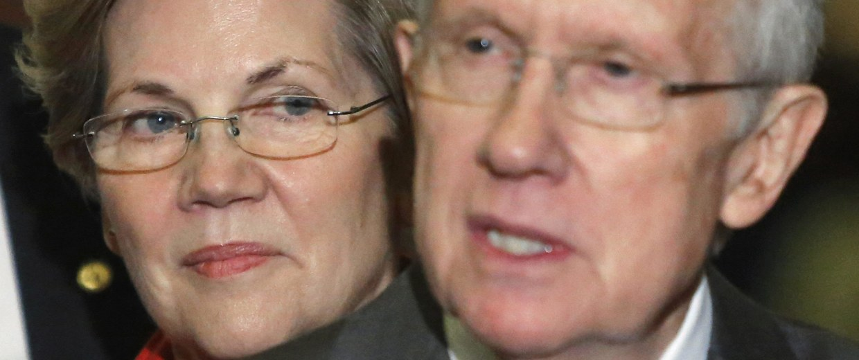 Image: U.S. Senator Warren stands behind Senate Majority Leader Reid after leadership elections for the Congress in Washington