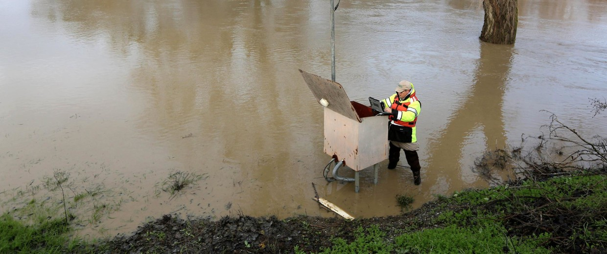 Image:  Eric Lindbloom of the U.S. Geological Survey checks a water metering station along Cache Creek near Woodland, Calif.