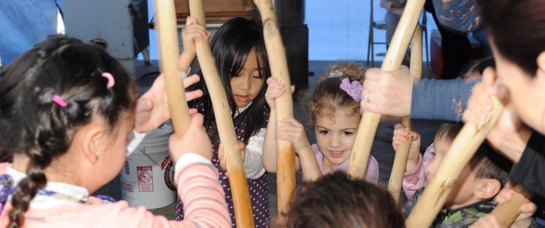 Children begin to break apart rice with sticks at Koda Farms Mochitsuki