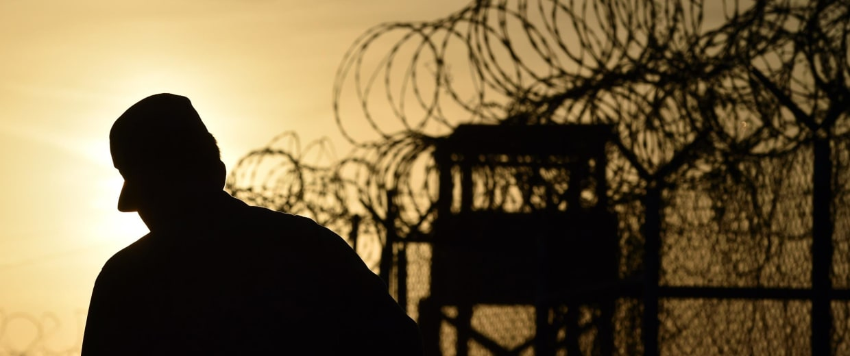 Image: A US soldier walks along a fence at the US Naval Station in Guantanamo Bay