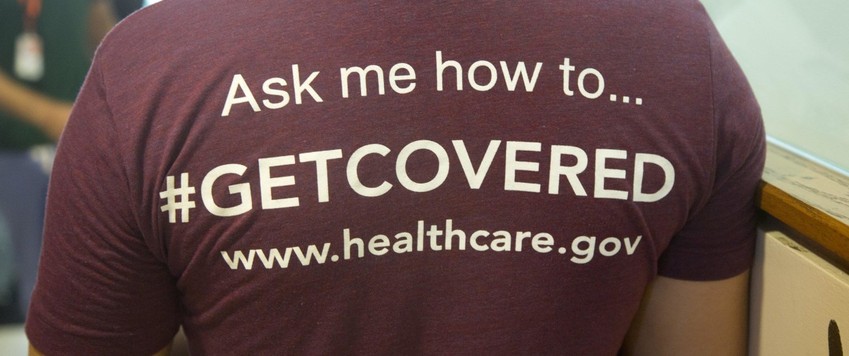 Image: A volunteer healthcare worker wears a T-shirt encouraging people to sign up for the new healthcare program.