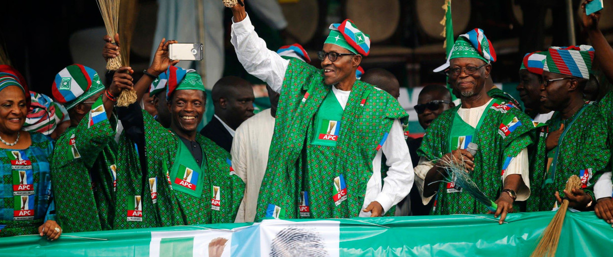 Image: Nigeria's former military ruler and presidential candidate of All Progressives Congress Muhammadu Buhari waves a broom as party members stand on a stage during a campaign rally in Ibadan