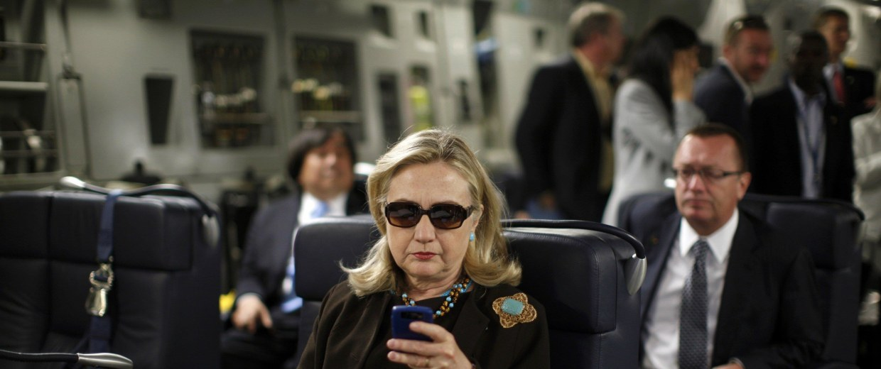 Image: File photo of U.S. Secretary of State Hillary Clinton checking her PDA upon her departure in a military C-17 plane from Malta bound for Tripoli