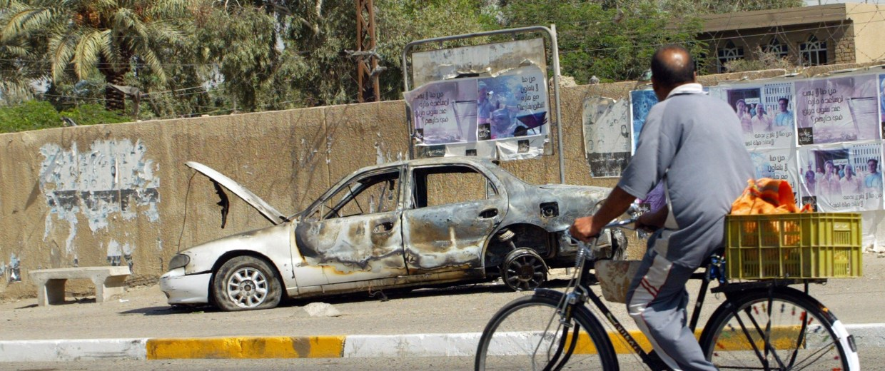 Image: An Iraqi man rides a bicycle passing by a remains of a car in Baghdad