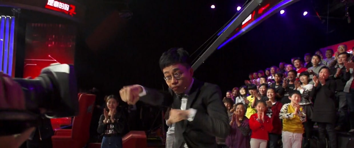 Image: Comedian Joe Wong makes am entrance during the taping of his show in Beijing.