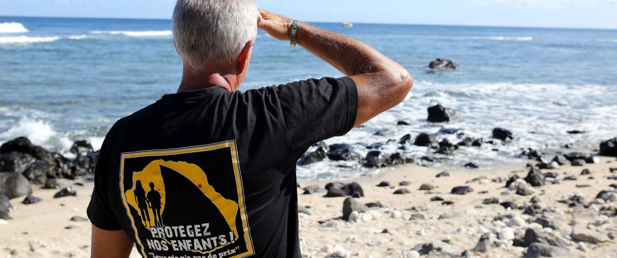 Image: A man stands on the beach in Les Aigrettes