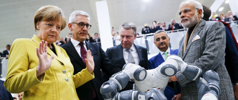 Image: German Chancellor Merkel and Indian Prime Minister Modi look at a YuMi robotic arm