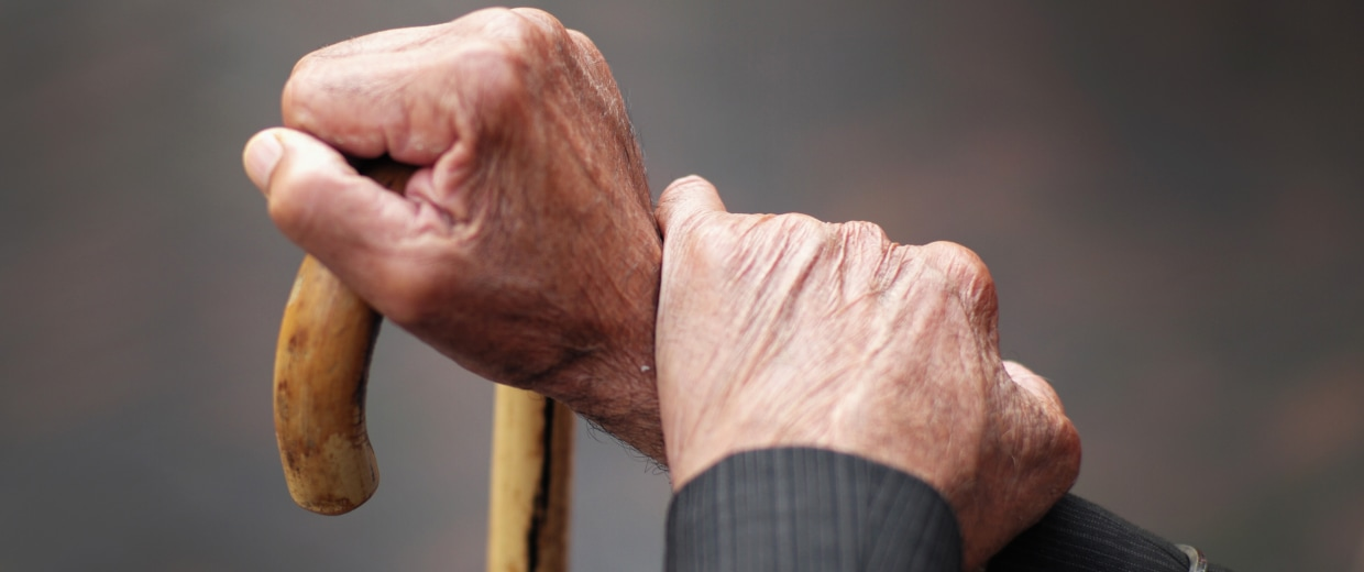 Image: A pensioner holds his walking stick