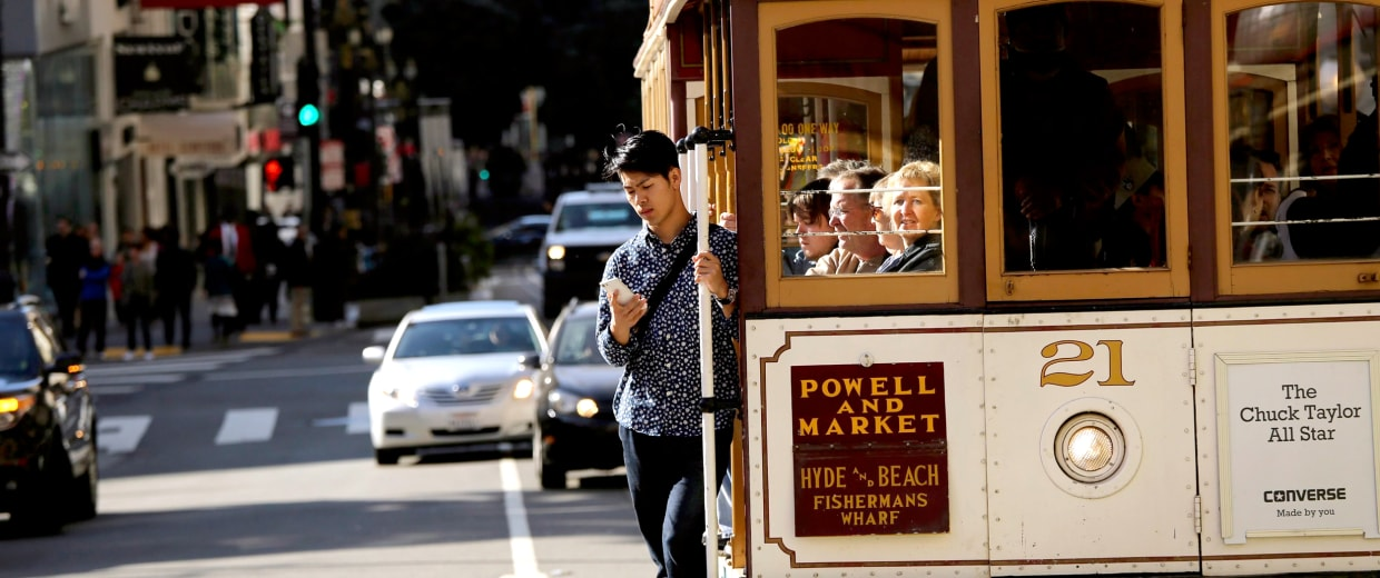 Image: A man looks at his mobile phone while riding the Powell and Market Street cable car line in San Francisco
