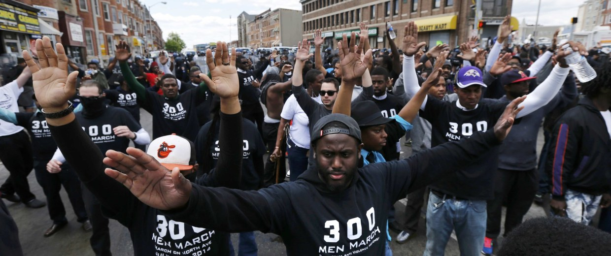 Image: Members of the community gesture in front of a line of police officers in riot gear, near a recently looted and burned CVS store in Baltimore