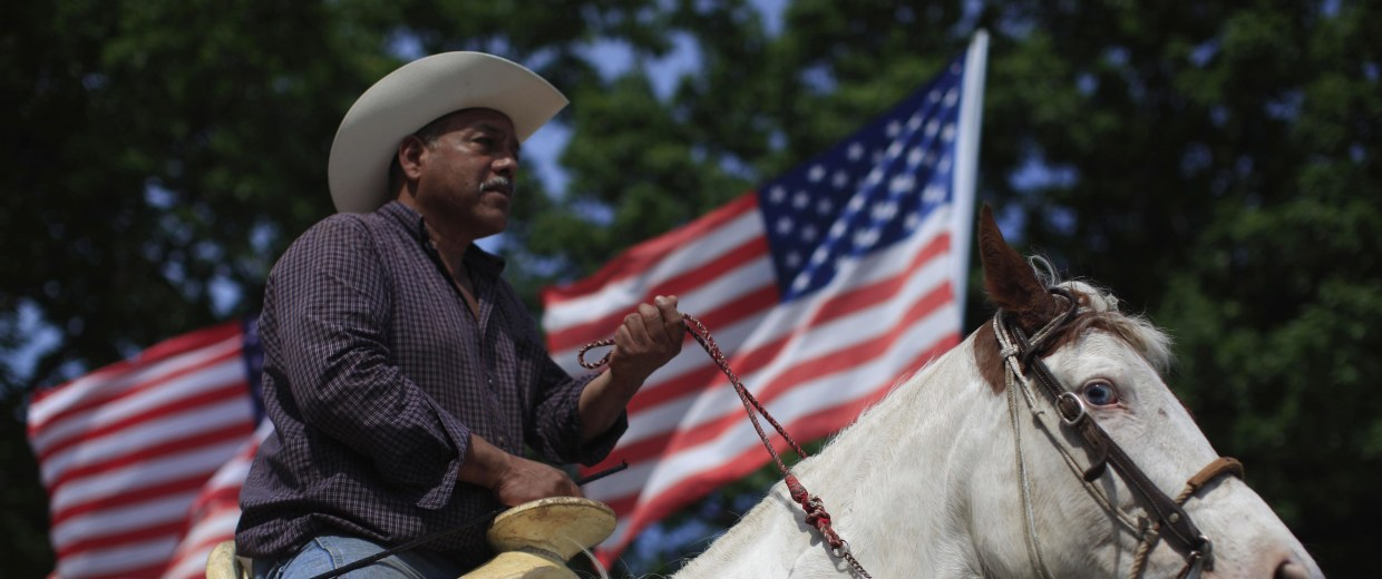 Image: A cowboy rides a horse through town as he watches a Cinco de Mayo celebration in Beardstown, Illinois