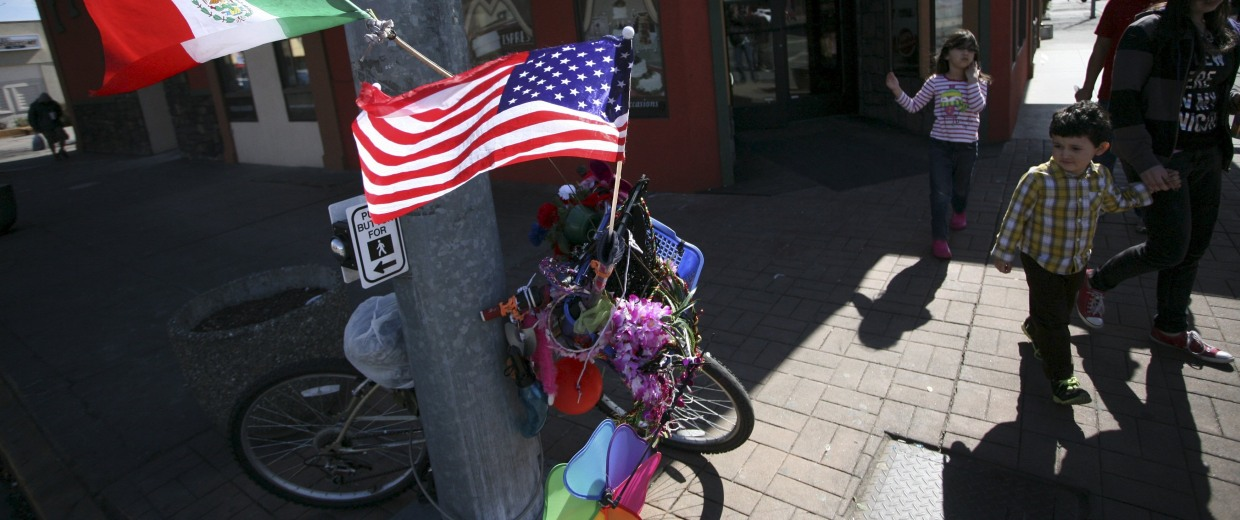 Image: Passers-by look at a bike adorned with trinkets and Mexican and the U.S. flags in Pasco, Washington