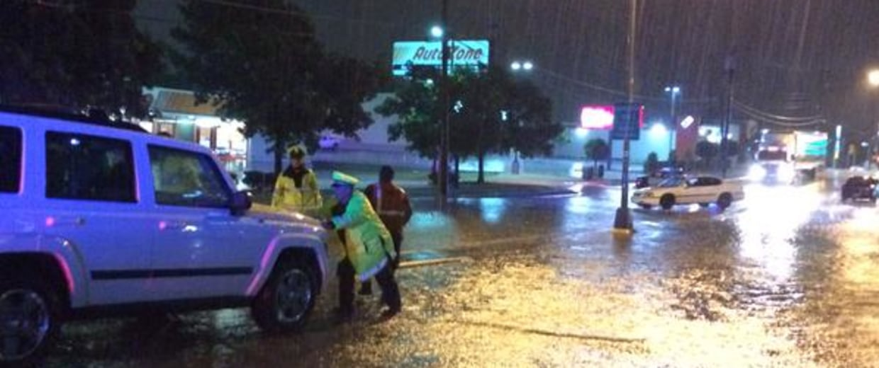 Image: Dallas police officers help move cars from flooded areas