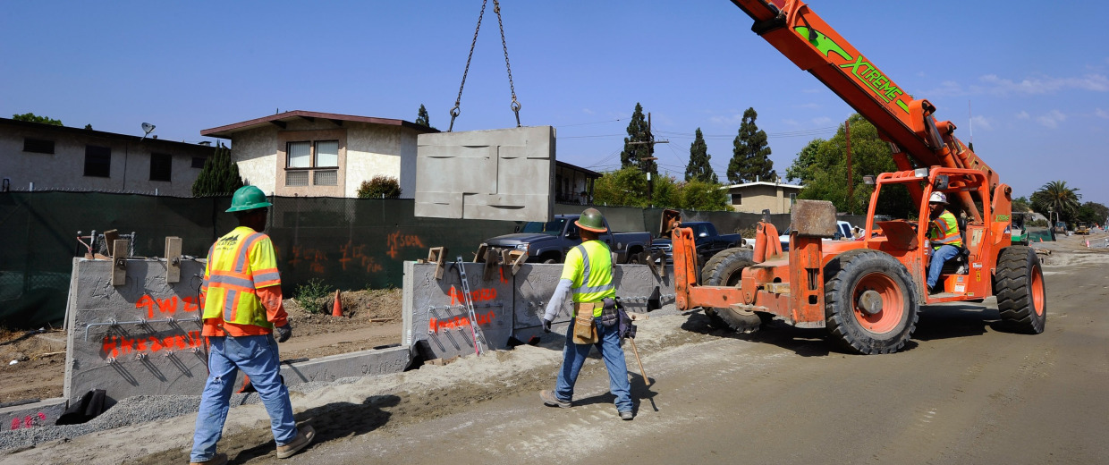 Image: Construction workers move a piece of concrete wall