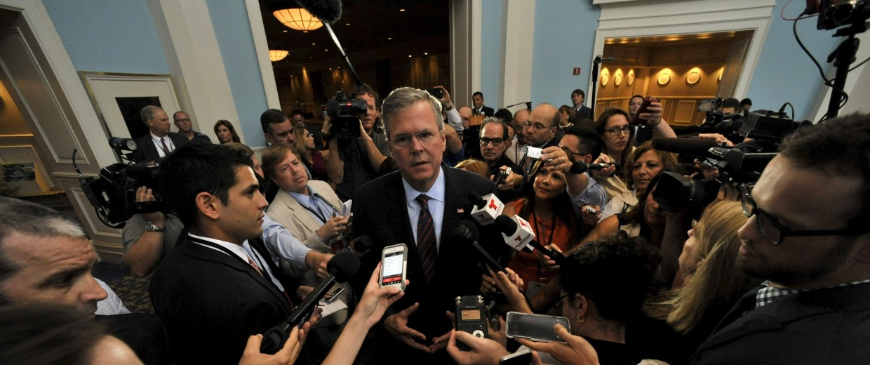 Image: Republican presidential hopeful Bush, the former governor of Florida, talks to a throng of media personnel  after addressing an economic summit in Orlando