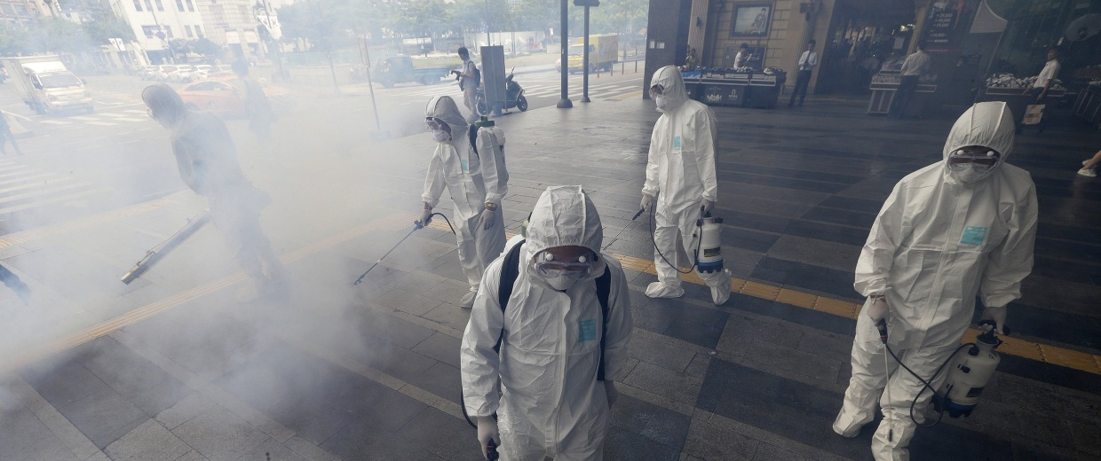 Image: Workers wearing protective gears spray antiseptic solution as a precaution against the spread of MERS