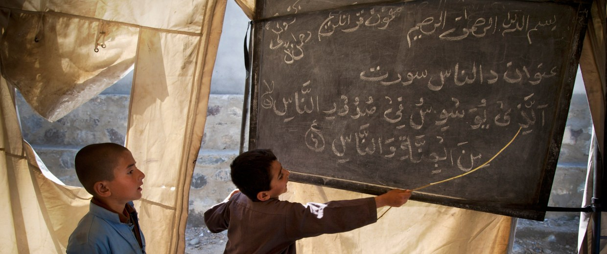 Image: Afghan boys study in a makeshift school in the village of Budyali