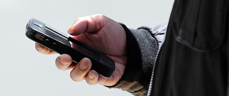 Image: A pedestrian uses a smartphone as he walk