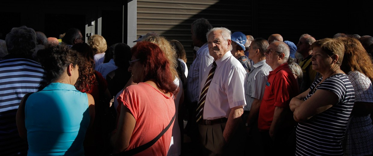 Image: Pensioners, who do not own an ATM card, wait to get part of their pensions in front of a branch of National Bank of Greece in Athens