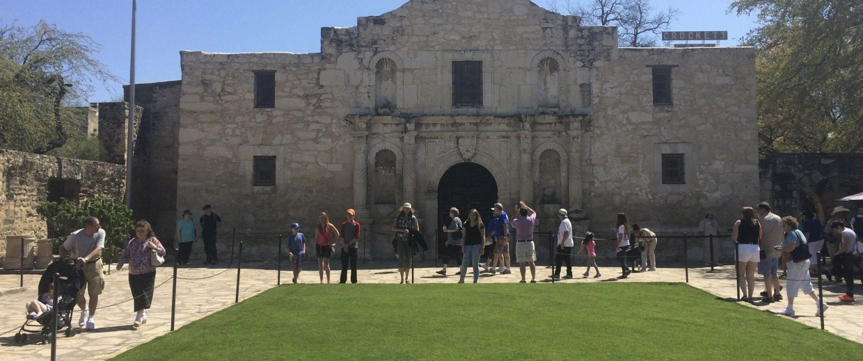 Image: Visitors walk at the entrance to the Alamo, the most-visited tourist site in the state, in San Antonio