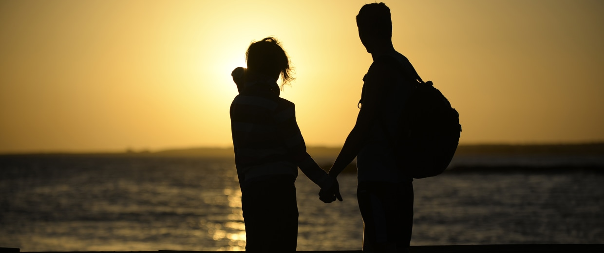 Image: A couple hold hands near the shore of El Yaque Beach
