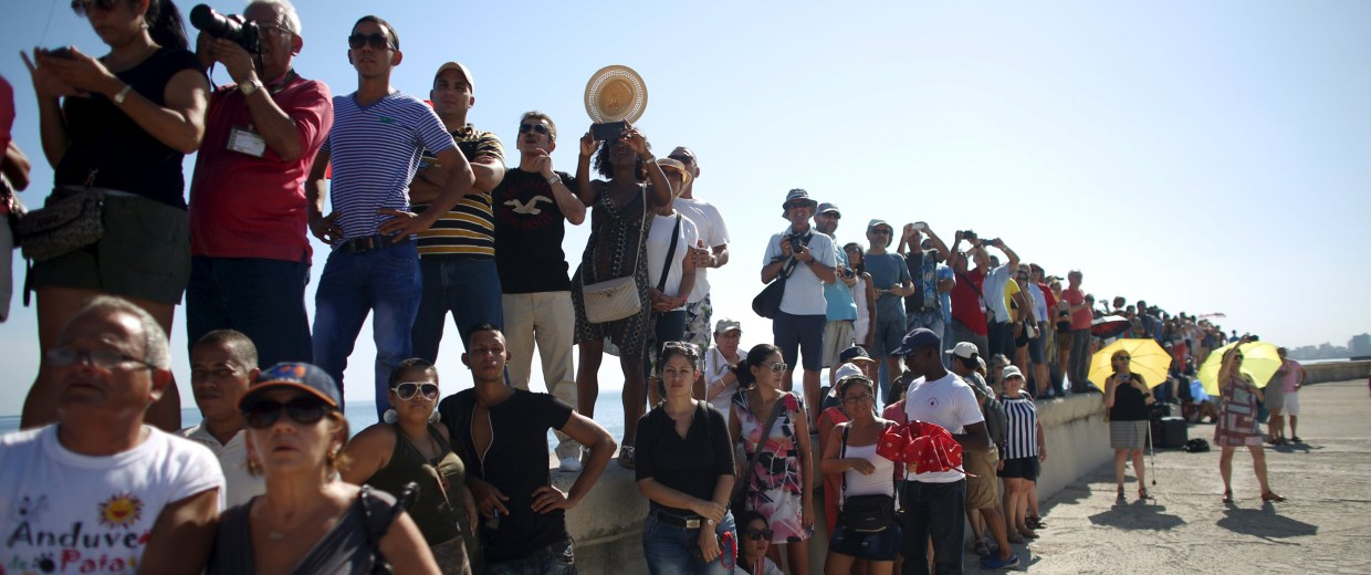 Image: People stand along the Malecon outside the U.S. embassy during a flag-raising ceremony in Havana