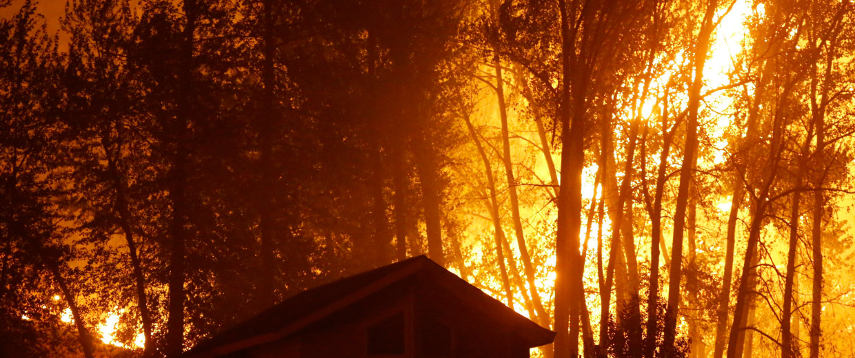 Image:  Wildfire burns behind a home in Washington