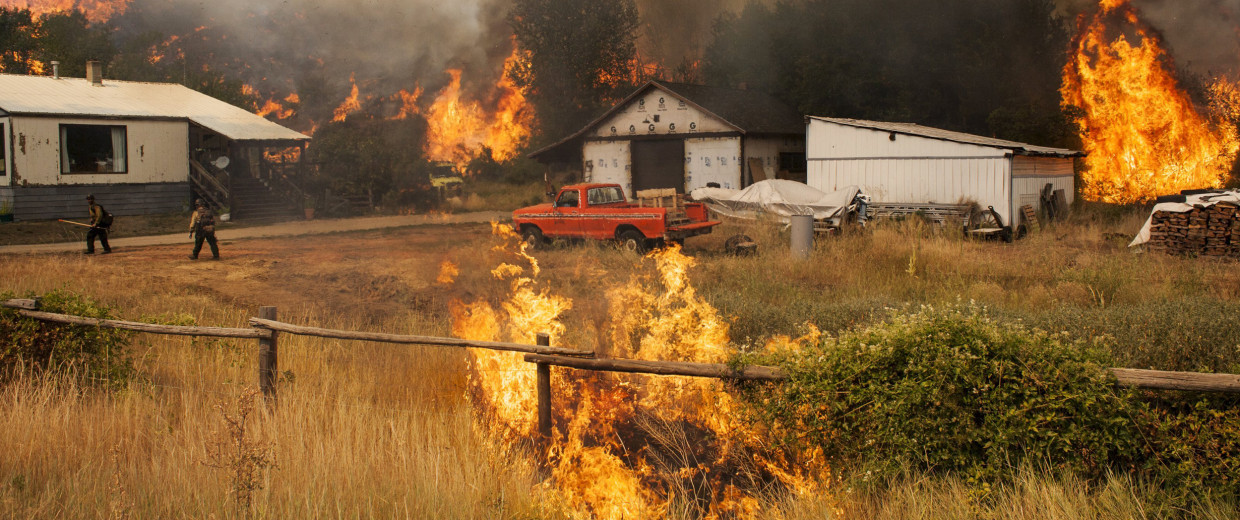 Image: Firefighters attempt to protect a home and outbuildings from the Twisp River fire near Twisp, Washington