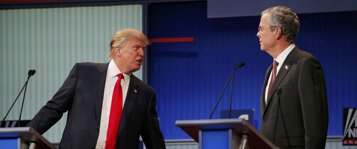 Image: Republican 2016 U.S. presidential candidate Trump talks with fellow candidate Bush during a commercial break at the first official Republican presidential candidates debate of the 2016 U.S. presidential campaign in Cleveland