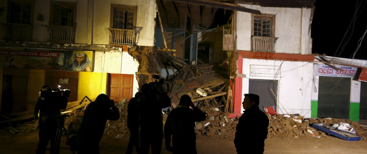 Image: Members of the media gather in front of a damaged building after an earthquake hit areas of central Chile, in Illapel town