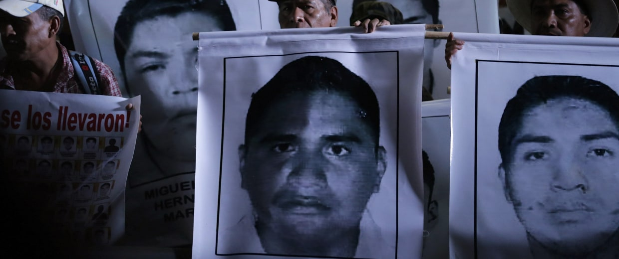 Image: Relatives of the 43 missing students of the Ayotzinapa teachers' training college hold pictures of the students, during a protest at Zocalo square in Mexico City