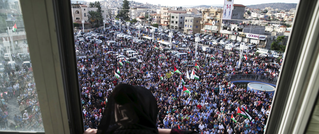 Image: A woman stands at a window overlooking a pro-Palestinian demonstration in the northern Israeli town of Sakhnin