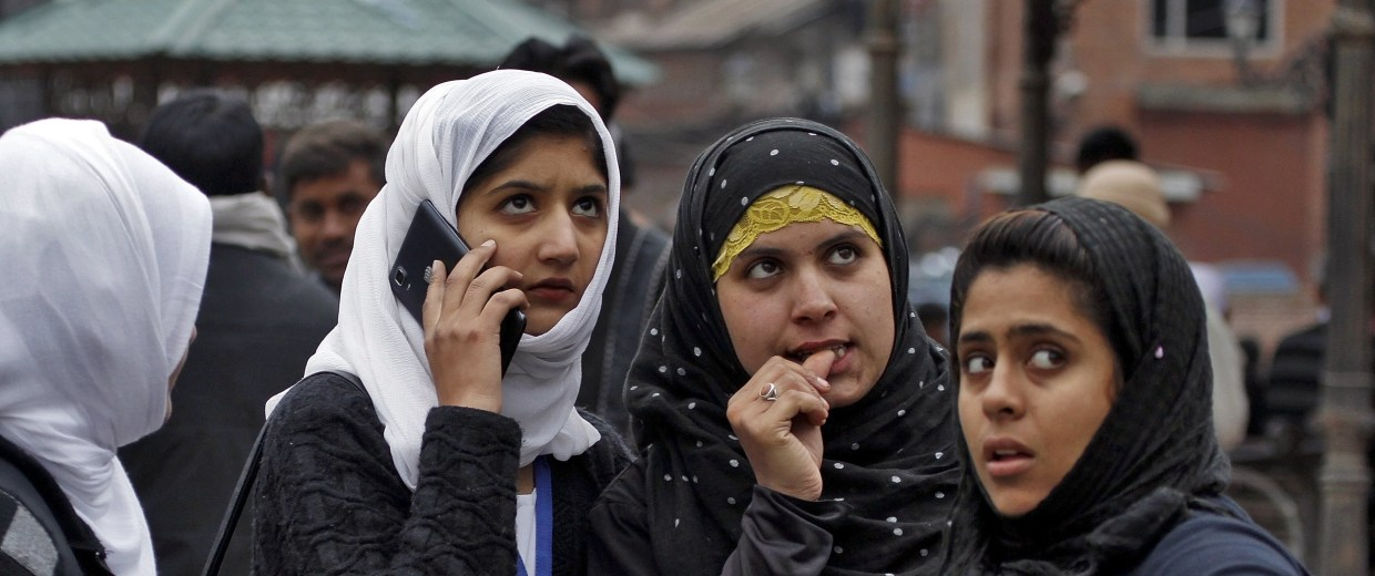Image: Kashmiri girls stand on a road divider after vacating their office buildings following an earthquake in Srinagar