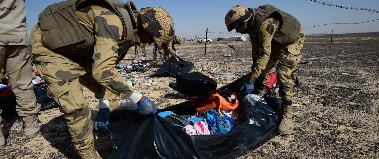 Image: Egyptian soldiers collect personal belongings of plane crash victims