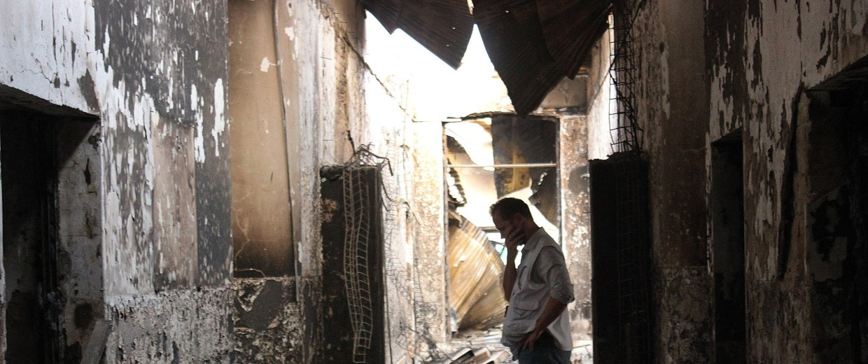 Image: An employee of Doctors Without Borders walks inside the charred remains of their hospital