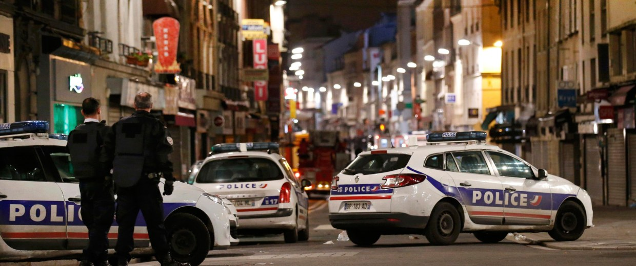 Image:  French police secure the area during an operation to catch Paris attack fugitives in Saint-Denis
