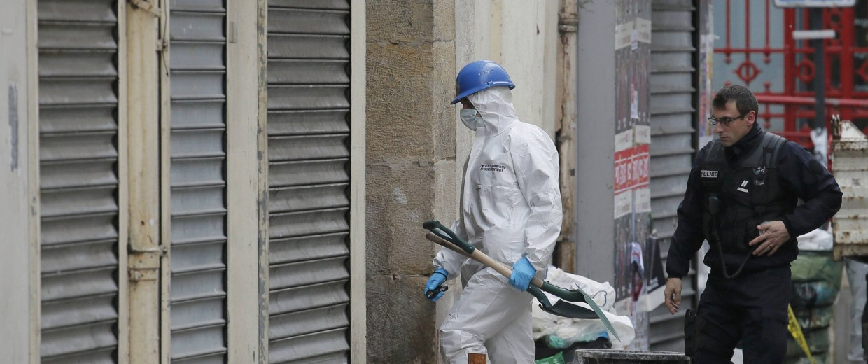 Image: A French policeman and a forensic expert enter a building as they work on the scene in Saint-Denis the day after a police raid to catch fugitives from Friday night's deadly attacks in the French capital