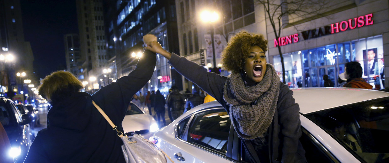 Image: A woman greets protesters out of a car window in Chicago.