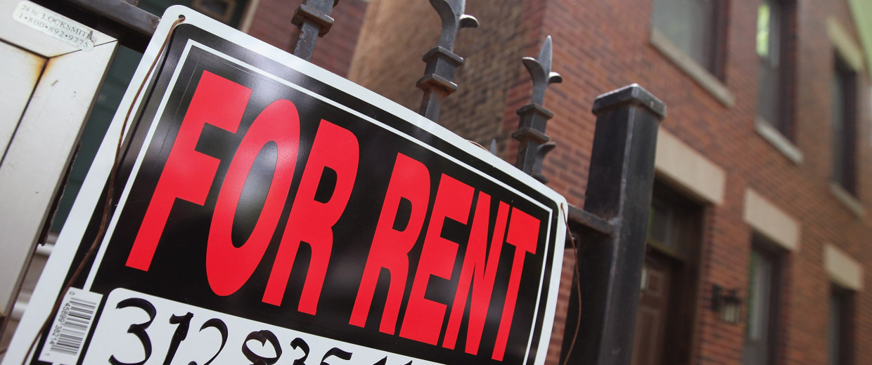 "Image: A ""For Rent"" sign stands in front of a house"