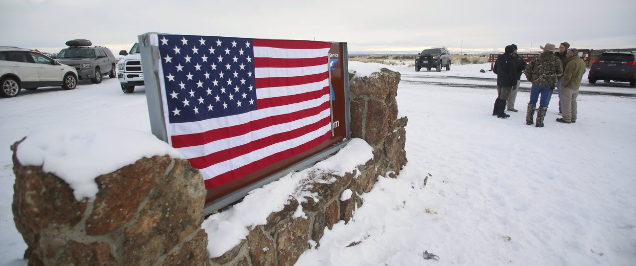 Image: A U.S. flag covers a sign at the entrance of the Malheur National Wildlife Refuge near Burns
